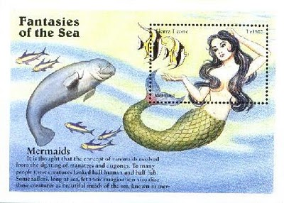 A manatee swimming beside a mermaid