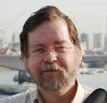 The face of a bearded, cheerful, middle-aged man with the Thames river and London in the background