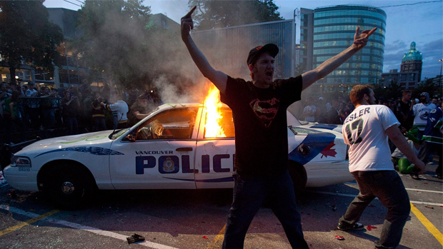 two young men stand and move around in front of a burning white police car