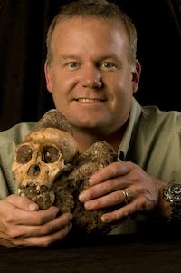 A man holding a small, semi-human fossil skull