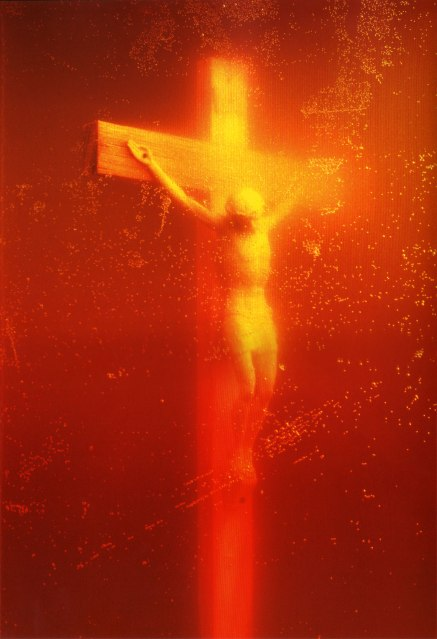 A crucifix with Christ on the cross in a golden glow from the urine he's submerged in
